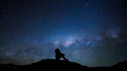 silhouette of man looking up at stars