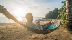 man in hammock using smartphone