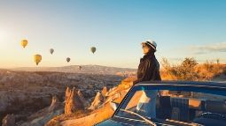 woman watching colorful hot air balloons flying over the valley at Cappadocia